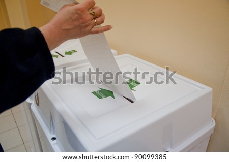 MOSCOW, RUSSIA - DECEMBER 4: Woman put election ballot with candidates of parties to the State Duma of Russian Federation into the box on December 4, 2011 in the local election commission.