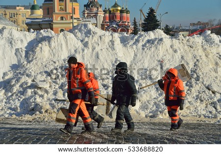 Moscow, Russia, December, 07, 2016  Workers with shovels walk past the mountains of snow removed in red square. See the domes of churches on Varvarka street