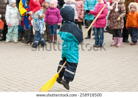 MOSCOW, RUSSIA - FEBRUARY 22: Unidentified boy run on broomstick on Russian religious and folk holiday Maslenitsa near Culture center Peresvet on February 22, 2015, Russia - stock photo