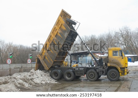 MOSCOW, RUSSIA - February 13, 2015: Unloading dirty snow from the body of the truck KAMAZ in negotable on snow-melting point, Moscow