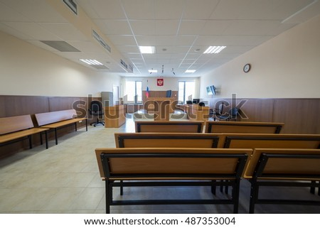 MOSCOW, RUSSIA - JUL 1, 2015: Court of law hall with wooden furniture, flag and clock on the wall.