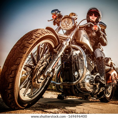MOSCOW, RUSSIA-JULY 7, 2013: Biker girl on legendary bike Harley Sportster (focus on the wheel).Harley-Davidson sustains a large brand community which keeps active through clubs, events, and a museum. - stock photo