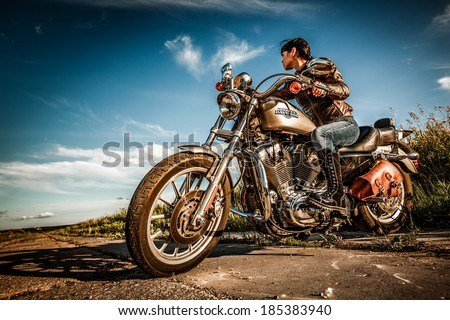 MOSCOW, RUSSIA-JULY 7, 2013: Biker girl on Legendary bike Harley Sportster. Harley-Davidson sustains a large brand community which keeps active through clubs, events, and a museum. - stock photo