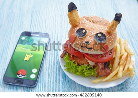 Moscow, Russia - July 29, 2016 Editorial image: Fan Art Pikachu Burger and Smartphone with Pokemon Go application. Selective focus.