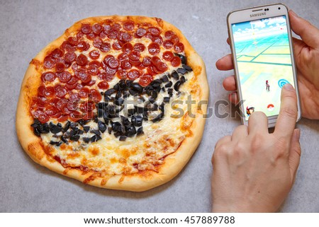 Moscow, Russia - July 15, 2016 Editorial image: Smartphone with Pokemon Go application and Fan Art Pokiball pepperoni pizza