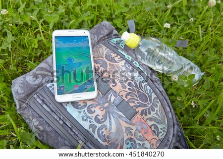 Moscow, Russia - July 13, 2016 Editorial image: Smartphone with Pokemon Go application on a green grass - stock photo