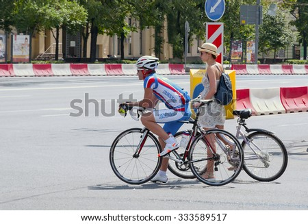 MOSCOW, RUSSIA - JULY 11, 2015: Two bicycles, sports man on a road bike and a romantic lady on cruiser bike waiting at the traffic light.