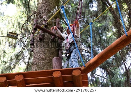 Moscow, Russia - June 12, 2015. The girl is climbing in adventure (rope) park on the wood background. Child has protection - helmet and safety equipment. Travel and adventure concept.