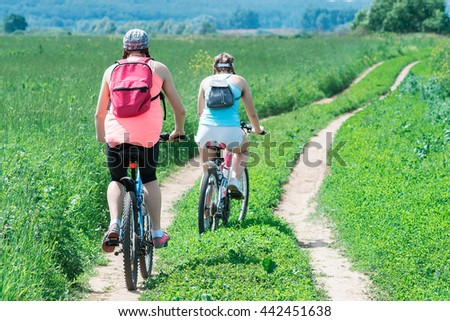 Moscow, Russia - June 18, 2016: Two girls on bicycles riding away by the field dirty road.