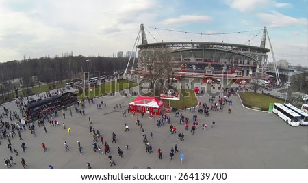 MOSCOW, RUSSIA - MAR 30, 2014: Lot of people walk away from Locomotive sports stadium after soccer match at spring day. Aerial view - stock photo