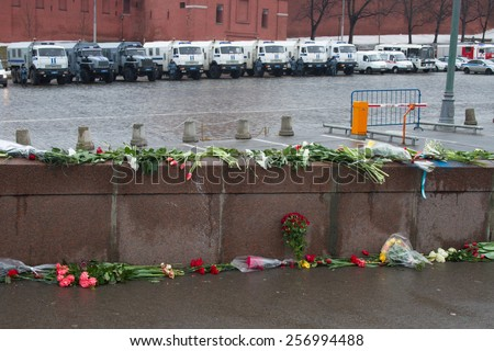 Moscow, Russia - March 1, 2015. The flowers near a place of murder of the politician Boris Nemtsov and the car of police protecting the Kremlin from march of opposition. March to the memory of Nemtsov - stock photo
