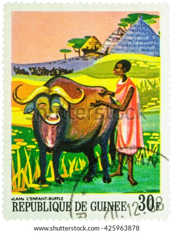 """MOSCOW, RUSSIA - MAY 12, 2016: A stamp printed in Guinea shows Lan, african bull and black woman, series """"Paintings of African Legends"""", circa 1968 - stock photo"""
