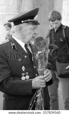 MOSCOW, RUSSIA - MAY 09: A war veteran holding flowers. Victory Day celebration in the Gorky park on May 09, 2013 in Moscow.