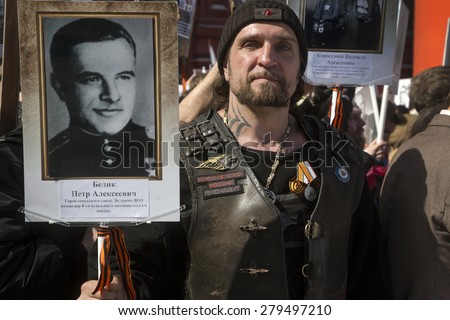 MOSCOW,RUSSIA-MAY9:Alexander Zaldostanov holds portrait of the hero of the Second World War as he takes part in the Immortal Regiment march during the Victory Day celebrations in Moscow on May 9,2015 - stock photo