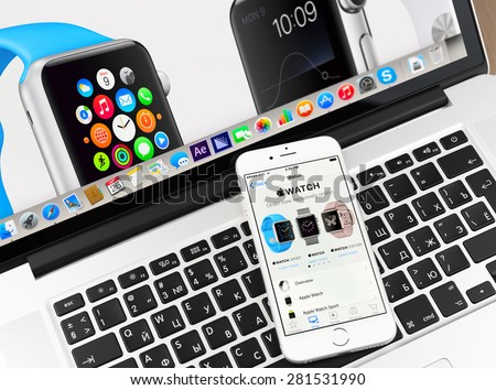 Moscow, Russia - May 26, 2015: Apple watch on iPhone 6 and Macbook display. Apple Watch is a smartwatch developed by Apple Inc. - stock photo