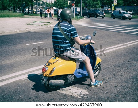 Moscow, Russia - May 30, 2016: Bearded man on old-fashioned Honda scooter. Vintage processed. - stock photo