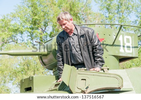MOSCOW/RUSSIA MAY 9:  Man comes out from restored BT-5 cavalry tank on display during festivities devoted to  anniversary of Victory Day on May 9, 2011 in Moscow.
