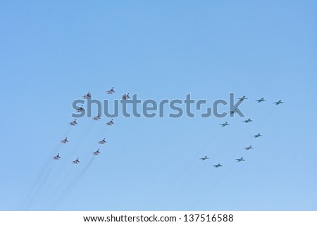 MOSCOW/RUSSIA - MAY 9: 12 Mikoyan MiG-29 (Fulcrum) fighters and 11 Sukhoi Su-25 (Frogfoot) jet aircrafts form figure 65 on parade devoted to 65th anniversary of Victory Day on May 9, 2010 in Moscow. - stock photo