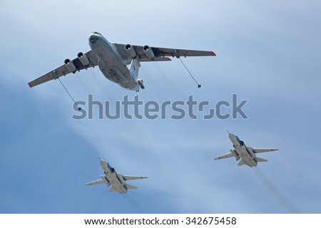 MOSCOW, RUSSIA - MAY 9, 2015: Military parade of 70th anniversaries of a victory day. Flight of aircraft over the city. The aircraft tanker Ilyushin Il-78 and Sukhoi Su-24 (Fencer) in the sky - stock photo