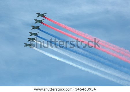 MOSCOW, RUSSIA - MAY 9, 2015: Military parade of 70th anniversaries of a victory day in WWII. A group of assault plane Sukhoi Su-25 Grach (Frogfoot) in the sky smoke colors of the Russian flag - stock photo