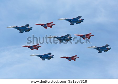 MOSCOW, RUSSIA-MAY 9, 2015: Military parade of 70th anniversaries of a Victory Day in WWII. Flight of aircraft over the city. Aerobatic team Swifts and Russian Knights on the fighters MiG-29 and Su-27 - stock photo