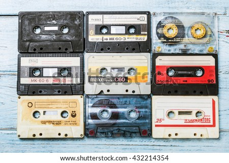 Moscow, RUSSIA - May 24, 2016: Old Cassette tapes over blue textured wooden table. Cassette tapes of different firms Maxell, Sakura, Svema etc.