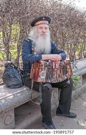MOSCOW/RUSSIA - MAY 9: Old grey-haired bearded accordion player in vintage navy uniform decorated with medals sits on bench during festivities devoted to Victory Day on May 9, 2013 in Moscow.
