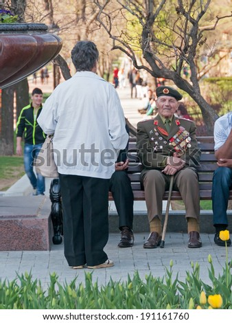MOSCOW/RUSSIA - MAY 9: Old man veteran of WWII decorated with numerous orders and medals in uniform sits on bench during festivities devoted to Victory Day on May 9, 2013 in Moscow.
