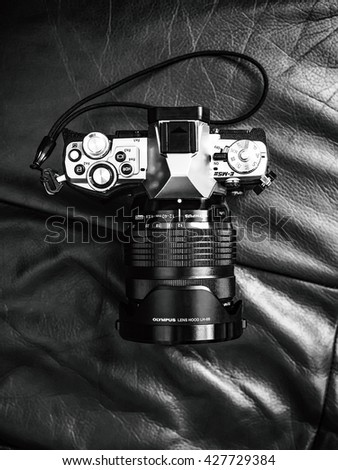 Moscow, Russia - May 05, 2016: Olympus OM-D E-M5 Mark II mirrorless camera on leather armchair, monochrome picture with BW film imitation - stock photo