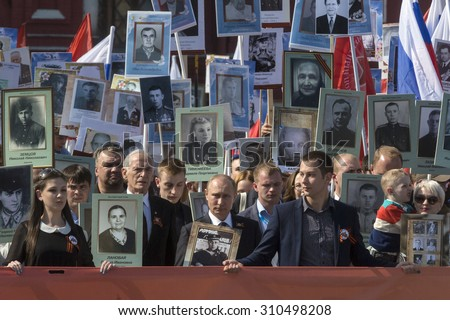 MOSCOW,RUSSIA-MAY 9:Russian President Vladimir Putin (Center) holds a portrait of his father as he takes part in the Immortal Regiment march during the Victory Day celebrations in Moscow on May 9,2015 - stock photo
