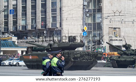 MOSCOW/RUSSIA - MAY 7: T-14 Armata main battle tank based on next generation heavy military vehicle combat platform and people on roadside on parade rehearsal on May 7, 2015 in Moscow.