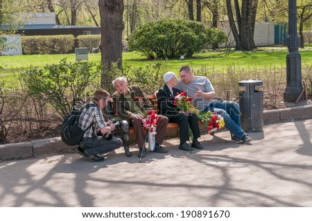 MOSCOW/RUSSIA - MAY 9: Two people talk to World War II veterans sitting with bunch of flowers on bench in Gorky Park during festivities devoted to Victory Day on May 9, 2013 in Moscow.