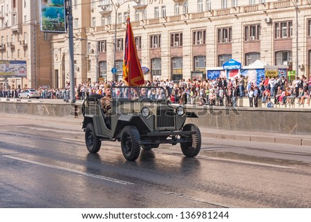 MOSCOW/RUSSIA - MAY 9: Two Soviet officers in WWII uniform with colours move in retro car (GAZ-67) on display during festivities devoted to 65th anniversary of Victory Day on May 9, 2010 in Moscow.