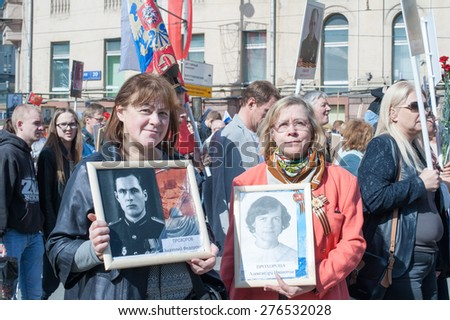 MOSCOW, RUSSIA - MAY 09, 2014: Women with portraits of their relatives during march of 'Immortal Regiment' in Moscow to honor relatives who fought in WWII - stock photo