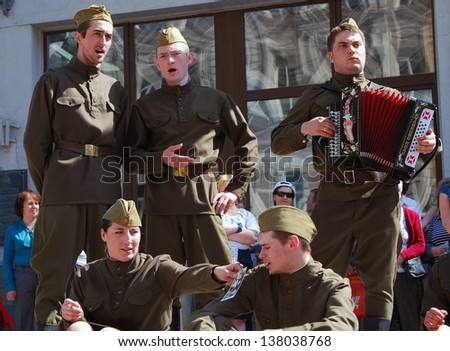 MOSCOW, RUSSIA - MAY 09: Young actors dressed as soldiers perform on Kamergersky lane in Moscow city center. Victory Day celebration on May 09, 2013 in Moscow.