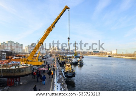 MOSCOW, RUSSIA - NOVEMBER 11, 2016: State Unitary Enterprise Mosvodostok performs recovery vessels on coastal winter parking. The crane lifts the boat out of the water.