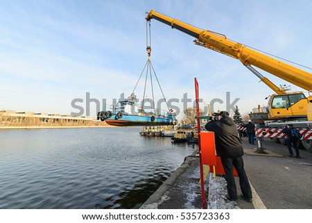 MOSCOW, RUSSIA - NOVEMBER 11, 2016: State Unitary Enterprise Mosvodostok performs recovery vessels on coastal winter parking. Videographer photographs work truck crane.