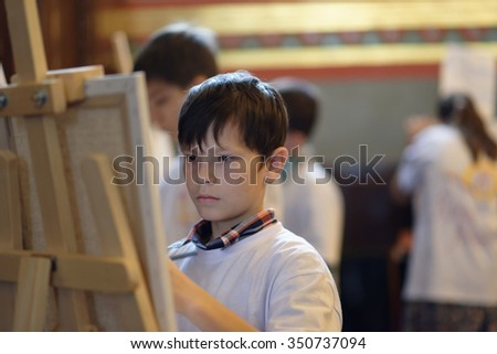 "MOSCOW, RUSSIA - NOVEMBER 27, 2015: Talented children from large families draw their guardian angel during the annual action ""Angel Wings"" in the Cathedral of Christ the Savior"