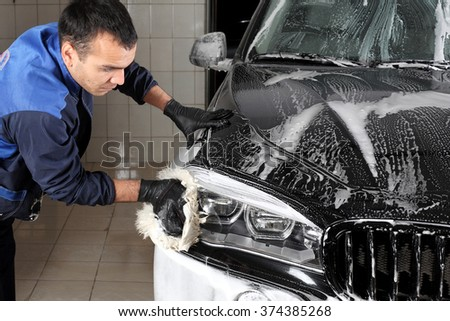 MOSCOW, RUSSIA - OCTOBER 4, 2015: The worker washing of the car big sponge. Car service.