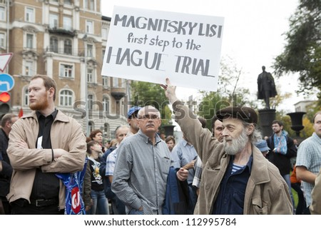 MOSCOW , RUSSIA - SEPT 15. Tens of thousands oppositionist  marched through Moscow in protest against President Putin . Man hold poster in support Magnitsky list. on September 15, 2012, Moscow - stock photo