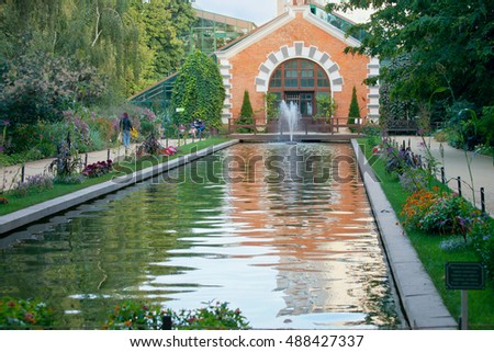 MOSCOW, RUSSIA - SEPTEMBER 6, 2016. People walking around a pond in a botanical garden in the center of Moscow. Warm September evening, colorful early autumn