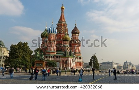 MOSCOW, RUSSIA - SEPTEMBER 12, 2013. St. Basil's Cathedral in Moscow, with people and residential buildings in the background.
