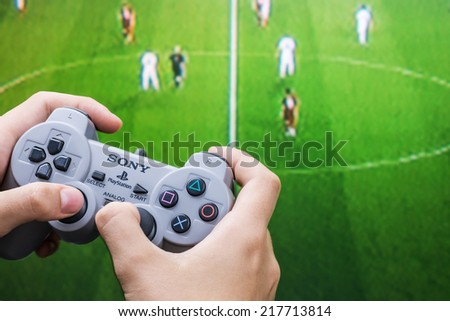 Moscow, Russia - September 11, 2014: Teenager playing football on the Playstation. Playstation game console of the fifth generation, developed by Sony Computer Entertainment Ken Kutaragi-led - stock photo