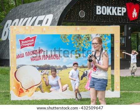 "MOSCOW, RUSSIAN FEDERATION - MAY 28: Participants of Ice cream festival. Advertsing of ice cream ""Gold Standard"" as background for photo shoot. MAY 28, 2016, Sokolniki Park, Moscow, Russia."