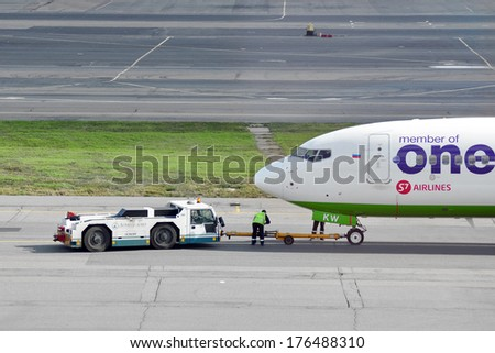 MOSCOW - SEPTEMBER 05: Airplane being towed at an airport Domodedovo in September 05, 2012 in Moscow. The airplane Airbus A321-231 of airline S7 - Siberia Airlines Reg VQ-BKW  - stock photo