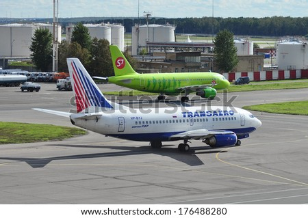 MOSCOW - SEPTEMBER 05: Airplanes in airport Domodedovo in September 05, 2012 in Moscow. The airplanes on the background of fuel storage at the airport Domodedovo  - stock photo