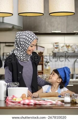 Moslem woman wearing hijab, teaching her daughter make halal food - stock photo