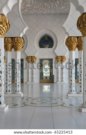 Mosque interior. White columns adorned with gold. - stock photo