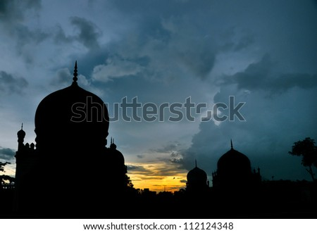 Mosque silhouette in cloudy evening - stock photo