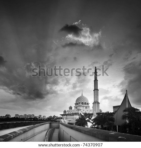 Mosque under dramatic sky in sunset in black and white.